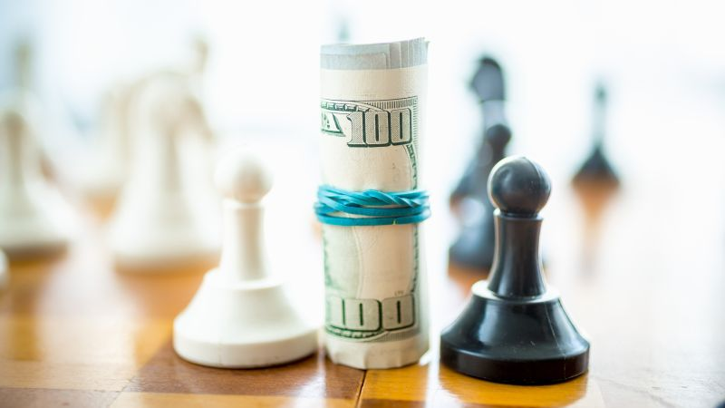 Twisted Dollar Bills Standing On Chess Board Between White And B