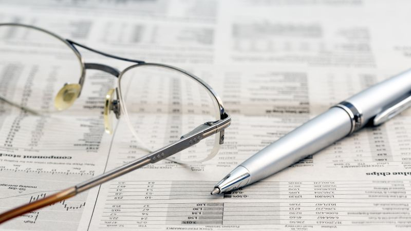 Business newspaper and glasses Conceptual image of opened newspaper with stock exchange data, glasses and pen